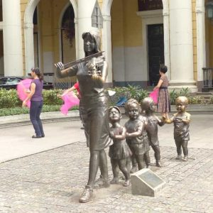 Un groupe de statues de bronze dans le centre ville. A l'arrière-plan, des petits groupes de gymnastique