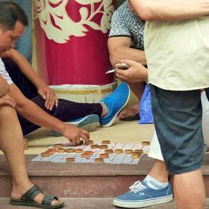 Dans les rues ou dans les squares, des petits groupes d'hommes jouent aux dames ou aux échecs chinois